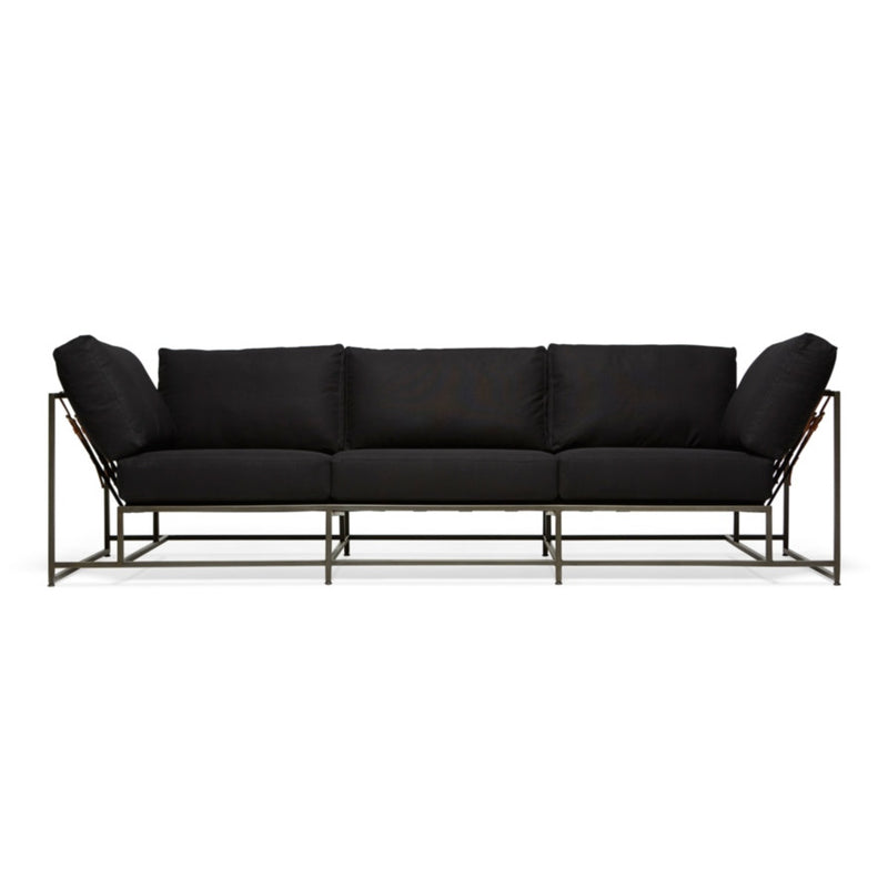 Soft black canvas upholstery atop a steel frame with a blackened finish. The supporting belts are composed of a black cotton webbing, cognac brown leather, and black buckles.