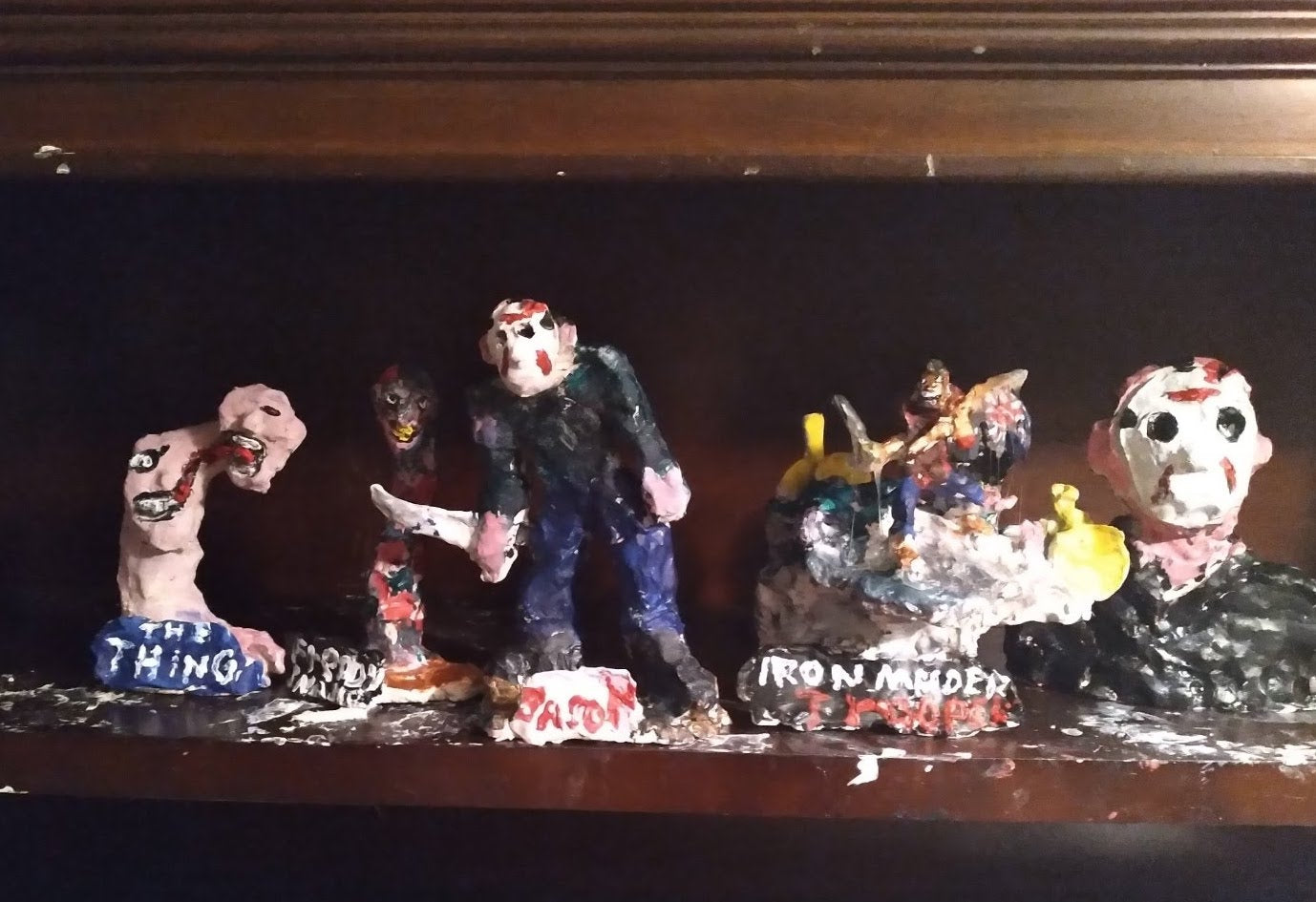 """a row of painted mixed-media sculptures lined up on a wooden shelf at the artist's home. Each sculpture depicts a different movie villain or metal band. On the far left is a sculpture of a figure with a long neck and a head that seems to be splitting in two. Text written on the base reads """"The Thing."""" To the right are sculptures of the head and neck of movie villain """"Freddie"""" from Nightmare on Elm street, with his yellow teeth and red and black striped shirt. In the center of the image is a sculpture of movie villain Jason from Friday the 13th: a person wearing a white hockey mask stained with blood, striding forward wielding a machete. To the right of Jason is a sculpture of what appears to be a group of figures on a rocky surface, labeled """"Iron Maiden."""" And finally, to the far right sits a larger bust of Jason, with a black shirt, pink skin, and the same blood stained hockey mask. The shelf is spotted with white paint."""