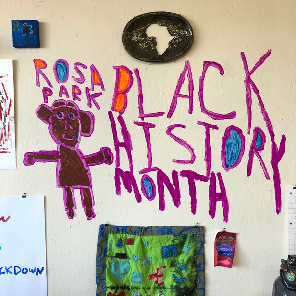 """A detail image of a portion of the gallery wall. There is a painting of a figure colored brown and purple, with the words """"Rosa Parks Black History Month"""" written in purple around them. Above this wall painting, there is a ceramic plate with a cut out in the shape of the African continent installed on the wall. To the right of this plate there is a small square blue painting of a flower. Along the bottom of this image, there is a green and blue quilted textile with hearts and other shapes appliquéd on it. To the right of this textile piece there is a small maroon and pink abstract marker drawing. The edges of the photo show corners of additional drawings that are installed on the wall, beyond the scope of this photograph."""