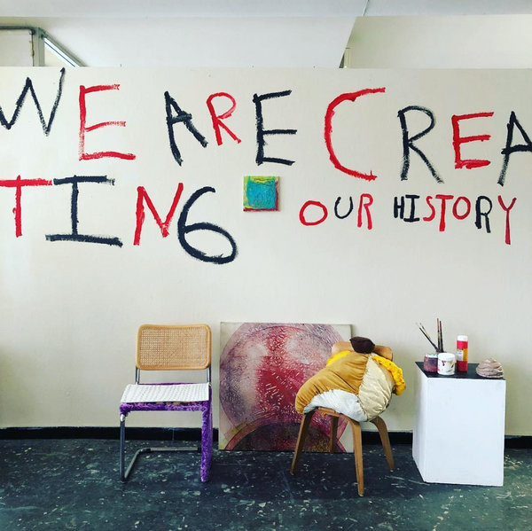 """this is a photograph taken early on in the set up of an exhibition, and features a wall mural, some paintings and sculptures that have not yet been installed. There is a white wall with the words """"WE ARE CREATING OUR HISTORY"""" painted in black and red capital letters. There is a small blue and yellow and red square painting hanging in the center of the wall. A large painting of a red and purple circle sits on the floor and leans against the wall at the center of this photo. To the left of this painting there is a tan and purple chair; to the right and in front of the painting there is a brown chair with a stuffed pillow sculpture sitting on it. There is a white pedestal to the far right of this image that has paint tubs and brushes on it. The floor in front of the wall is dark mottled grey."""
