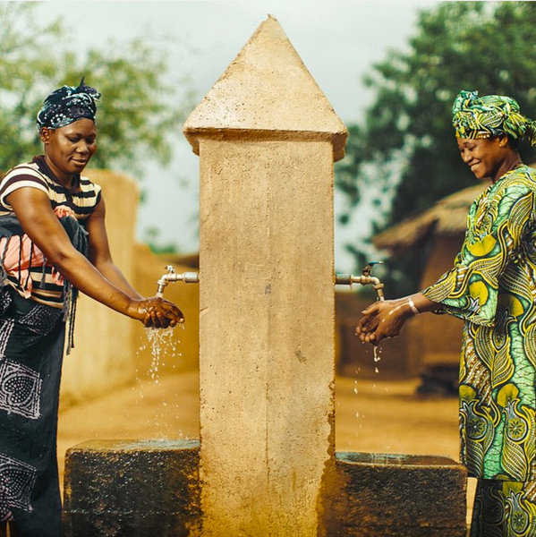 chasewaterfalls, two women collecting clean water from a constructed well