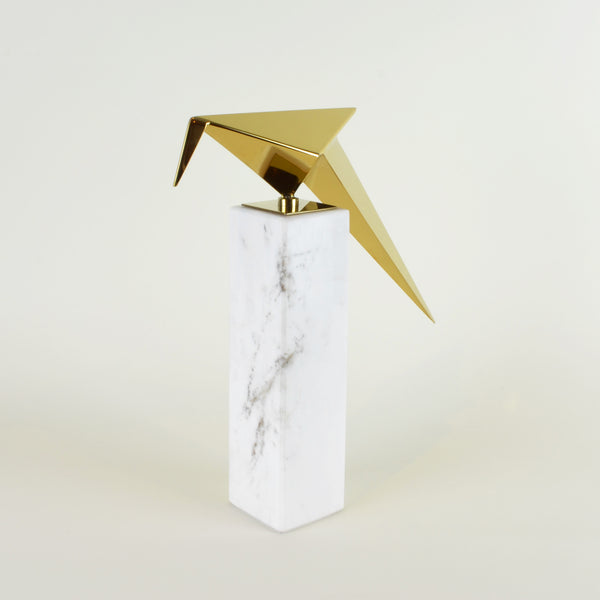 Leaning Origami Bird - View 1 - Contemporary Decorative Object. Inspired by the Japanese origami art. Gold colour ornament with Calacatta marble base. Origami Bird Sculpture. Materials: Nickel plated steel, Calacatta marble. Bird theme home accessories. Modern style home décor. Top interior design trend. Designer gift. Dimensions: W29.5 D8.5 H30cm. Small - medium size sculpture for styling shelves, display units, coffee tables and console tables.