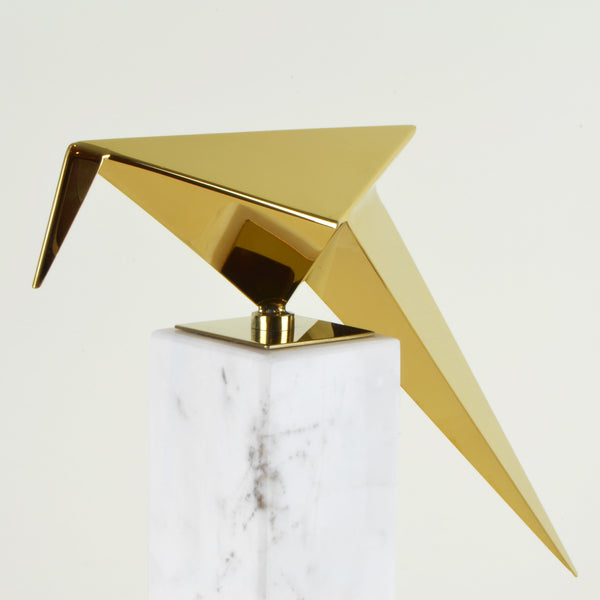 Leaning Origami Bird - Detail - Contemporary Decorative Object. Inspired by the Japanese origami art. Gold colour ornament with Calacatta marble base. Origami Bird Sculpture. Materials: Nickel plated steel, Calacatta marble. Bird theme home accessories. Modern style home décor. Top interior design trend. Designer gift. Dimensions: W29.5 D8.5 H30cm. Small - medium size sculpture for styling shelves, display units, coffee tables and console tables.