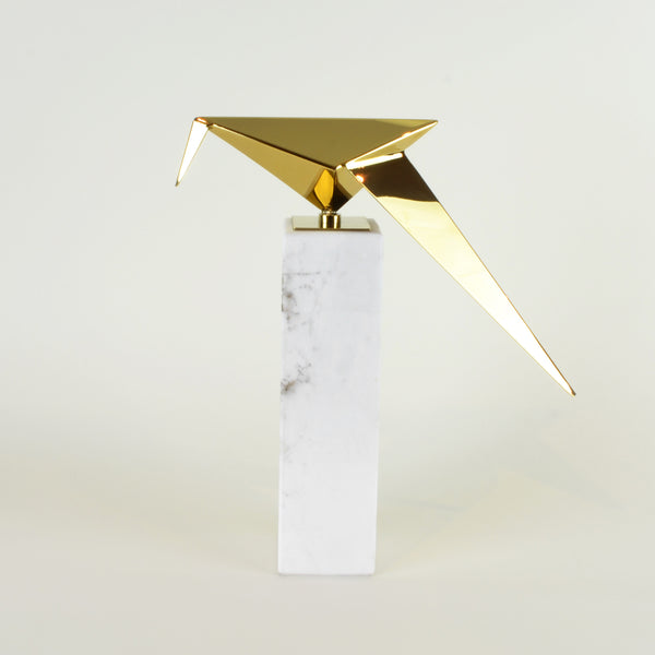 Leaning Origami Bird - View 2 - Contemporary Decorative Object. Inspired by the Japanese origami art. Gold colour ornament with Calacatta marble base. Origami Bird Sculpture. Materials: Nickel plated steel, Calacatta marble. Bird theme home accessories. Modern style home décor. Top interior design trend. Designer gift. Dimensions: W29.5 D8.5 H30cm. Small - medium size sculpture for styling shelves, display units, coffee tables and console tables.