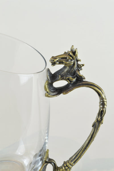 Horse Shot Glasses - Detail - Glassware set. Set includes 1x Jug and 6x Shot Glasses. Bronze colour. Bronze Horse Head and handle detail. Horse theme home accessories. Materials: High Grade Glass, Cast Bronze Handmade.  Shot Glass dimensions: Ø4 H7cm. Jug Carafe dimensions: W11 D7.5 H15cm. Dinner Party and home entertainment accessories. A designer gift to add to luxury homes. Royal Ascot theme home decor. Jug and shot glasses suitable for coffee and ginger shots.