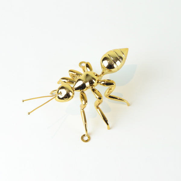 Gold Ant - View 3 - Best seller. Decorative Object / Sculpture. Gold Colour. Ant Decorative object. Can be used as a free standing ornament or wall decor. The Ant feet contains fixtures that allowed the sculpture to be hung on the wall and used as a sculptural wall art. Materials: Nickel plated steel. Dimensions: W16 D7.5 H8cm. Insect theme home accessories. Use several ants to create a wall art installation. Use single ant ornament to style coffee table books. Top Interior design trend.