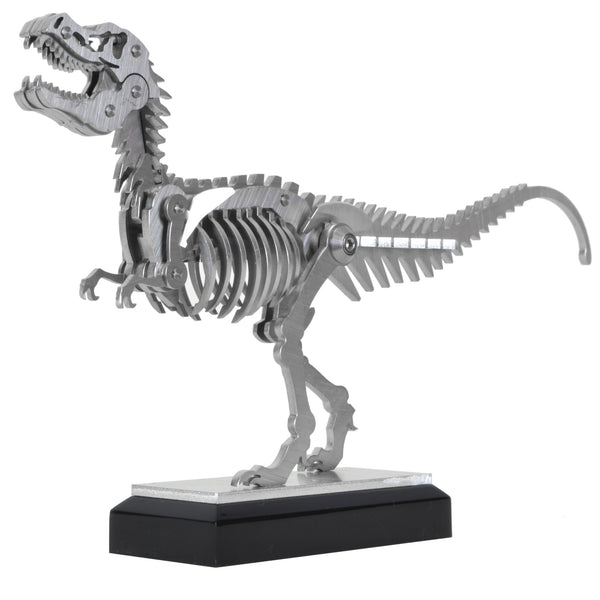 Mini T-Rex - View 1 - Decorative Object / Sculpture. Silver Colour. Dinosaur Sculpture. T-Rex skeleton ornament. Industrial chic style dinosaur object. Materials: Brushed Stainless steel. Acrylic base. Jurassic Park theme home accessories. Kids home decor. Dinosaur sculpture can be used to style coffee table books. Ideal gift for Jurassic World fans. Dimensions: W23 D4 H13cm. Small – Medium size Sculpture / Ornament for styling shelves, coffee tables and display units.