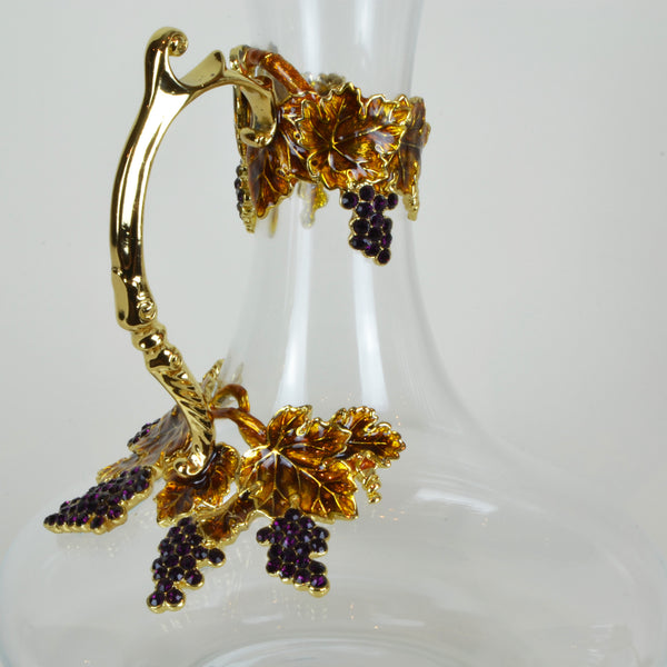 Amber Wine Carafe Detail - Glassware set. Set includes 1x Carafe and 4x Wine Glasses. Gold and Amber colour. Intricate metal and natural stone vine leaves detail. Natural Amber material and Swarovski coloured crystals.  Materials: High Grade Glass, Brass, Amber, Lacquer. Handmade.  Wine Glass dimensions: Ø7 H21cm. Glass Carafe dimensions: Ø20 H26cm. Dinner Party and home entertainment accessories. A designer gift to add to luxury homes.