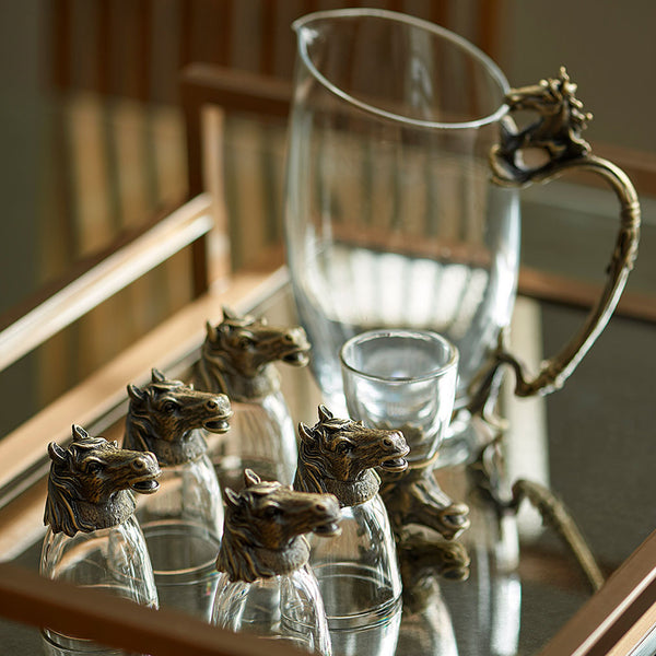 Horse Shot Glasses - Lifestyle 2 - Glassware set. Set includes 1x Jug and 6x Shot Glasses. Bronze colour. Bronze Horse Head and handle detail. Horse theme home accessories. Materials: High Grade Glass, Cast Bronze Handmade.  Shot Glass dimensions: Ø4 H7cm. Jug Carafe dimensions: W11 D7.5 H15cm. Dinner Party and home entertainment accessories. A designer gift to add to luxury homes. Royal Ascot theme home decor. Jug and shot glasses suitable for coffee and ginger shots.