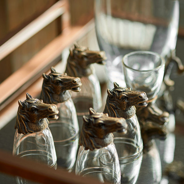 Horse Shot Glasses - Lifestyle 1 - Glassware set. Set includes 1x Jug and 6x Shot Glasses. Bronze colour. Bronze Horse Head and handle detail. Horse theme home accessories. Materials: High Grade Glass, Cast Bronze Handmade.  Shot Glass dimensions: Ø4 H7cm. Jug Carafe dimensions: W11 D7.5 H15cm. Dinner Party and home entertainment accessories. A designer gift to add to luxury homes. Royal Ascot theme home decor. Jug and shot glasses suitable for coffee and ginger shots.