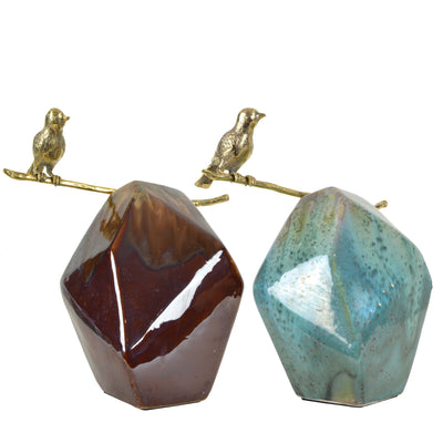 Bird on Small Rock - Colourways - Brass Sculpture / Decorative Object. Bird sculptural detail. Gold Bird Colour. Ceramic rock shaped base in two colourways: Teal and Brown. Materials: Brass, Ceramic. Dimensions: W32 D22 H34cm. Bird and nature theme home a