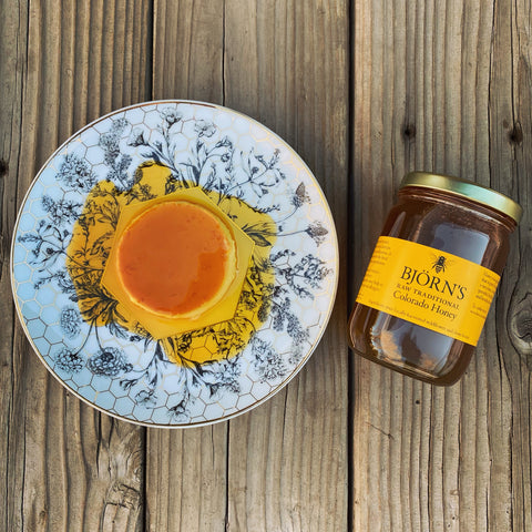 Honey Creme Caramel on a patterned plate with a jar of Bjorn's Raw Traditional Honey next to it