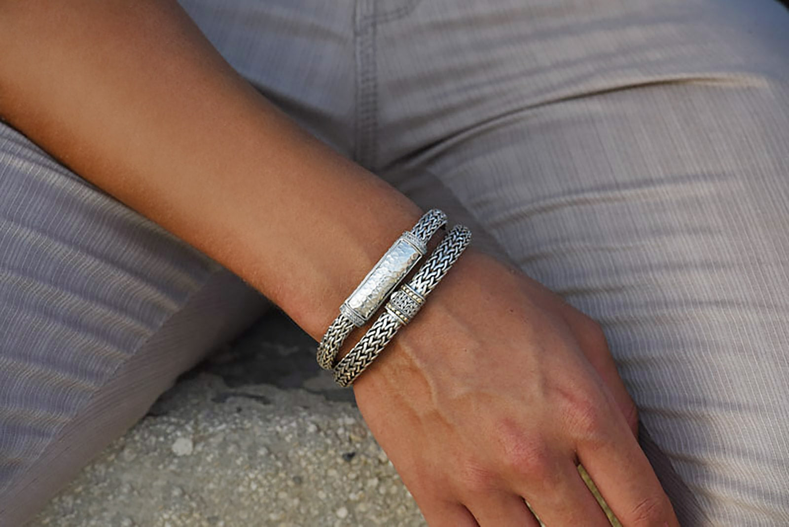 Model wearing Hammered silver Bali Bracelet and woven snake weave bracelet