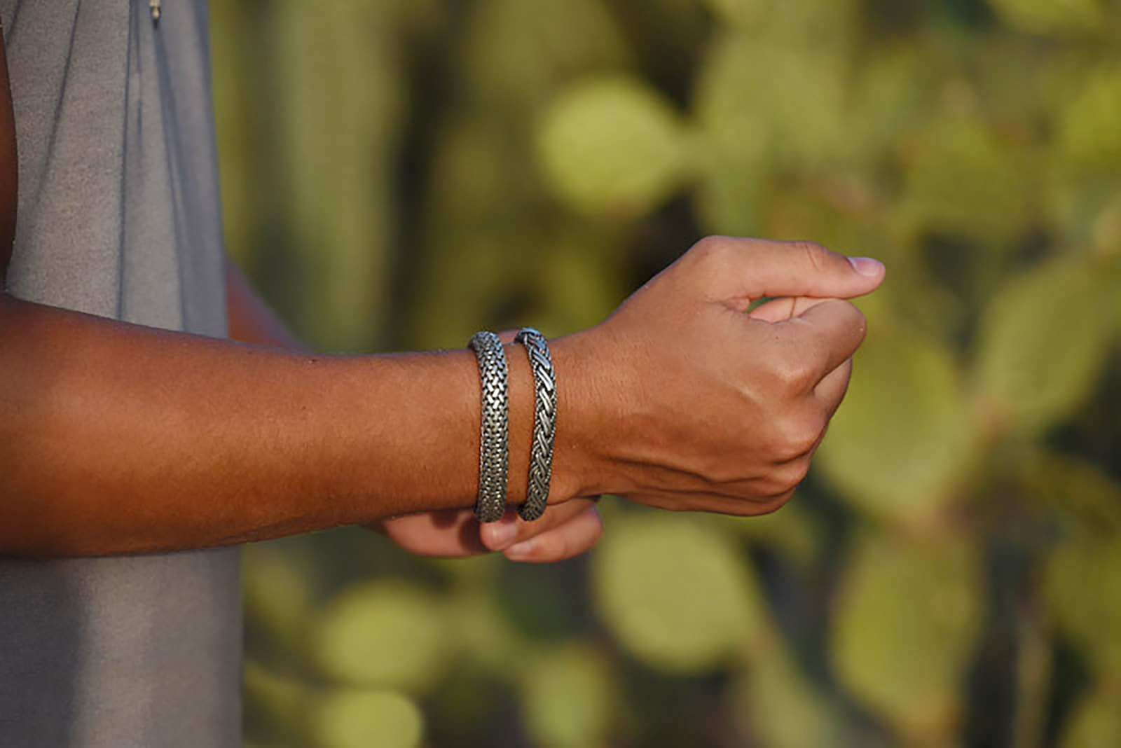 Model in grey t shirt touching bali bracelets