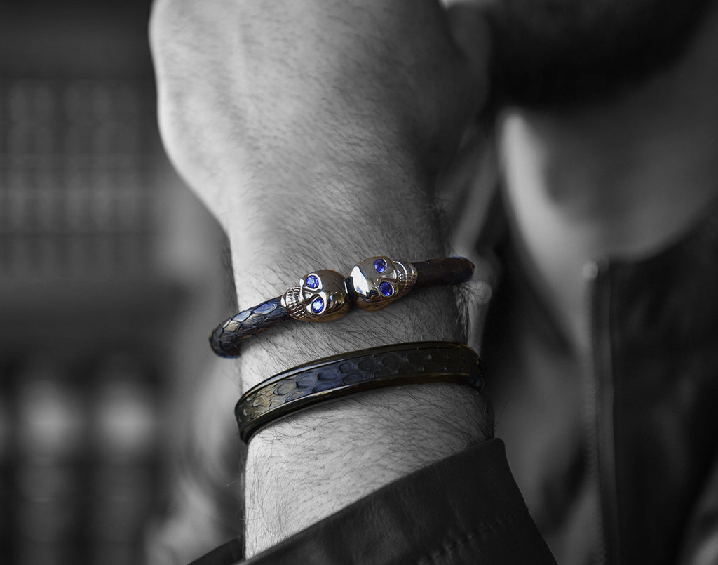black and white picture of model wearing sapphire skull bracelet with gunmetal python cuff