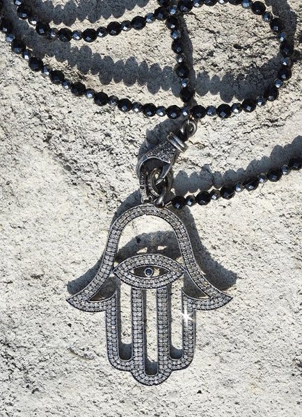 hamsa hand diamond necklace on rock background