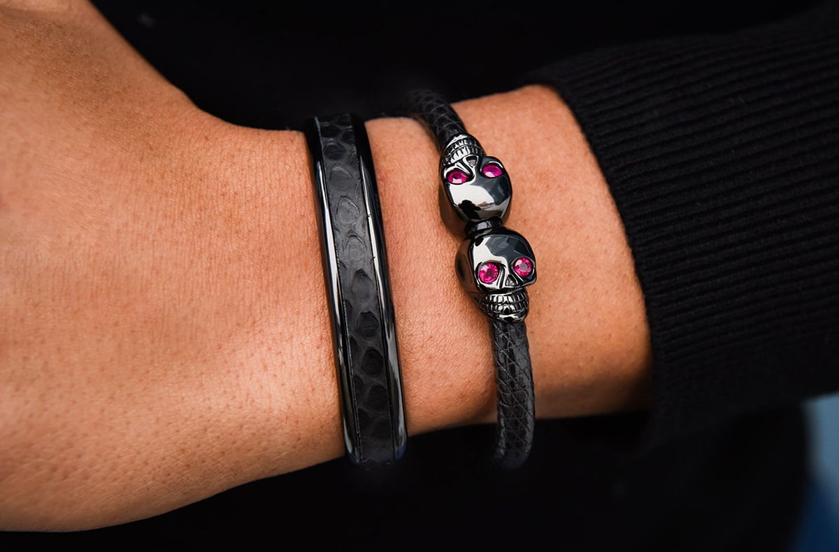 man wearing black skull lizard luxury bracelet set with rubies
