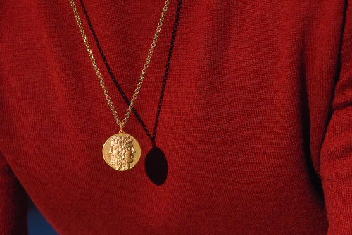 guy wearing gold roman coin necklace