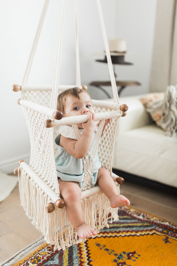 Macrame baby swing handmade in Nicaragua. Cream coloured macrame baby hammock with wood detail.