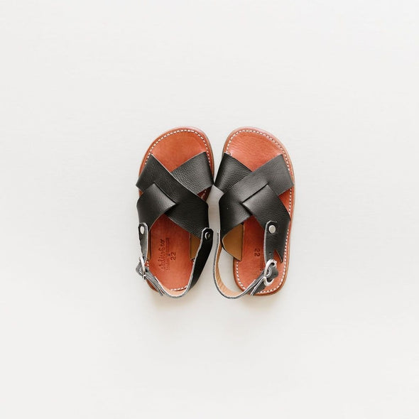 Adelisa & Co's handmade, unisex, leather Cruz sandals in black. These sandals have a simple criss cross style and are available in baby, child, and youth sizes. Crafted by artisans in Nicaragua.