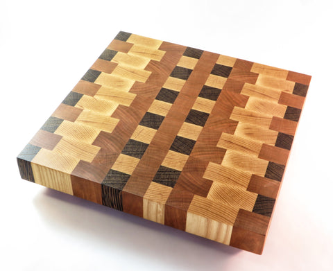 "One-of-a-kind engrain handmade wooden cutting board. Cherry and ash, with padauk highlights. Sturdy (and handsome) angled legs keep board well above countertop moisture. About 11 1/2"" x 11 1/4"" x 2 1/4"" H"