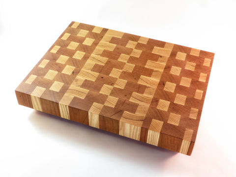 "Handmade endgrain wooden cutting board with two American hardwood favorites in a sophisticated grid. American ash and cherry. Angled legs keep board well above countertop moisture. About 9 3/4""x 13 1/8""x 2 3/8"""