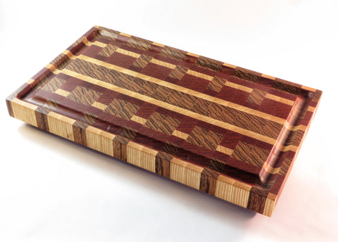 "Handmade endgrain wooden cutting board with gutter to keep juice with the meat (and off the table). Ash, padauk, and zebrawood. Beveled legs keep board above countertop moisture. About 8 3/4"" x 14 7/8""x 1 7/8"""