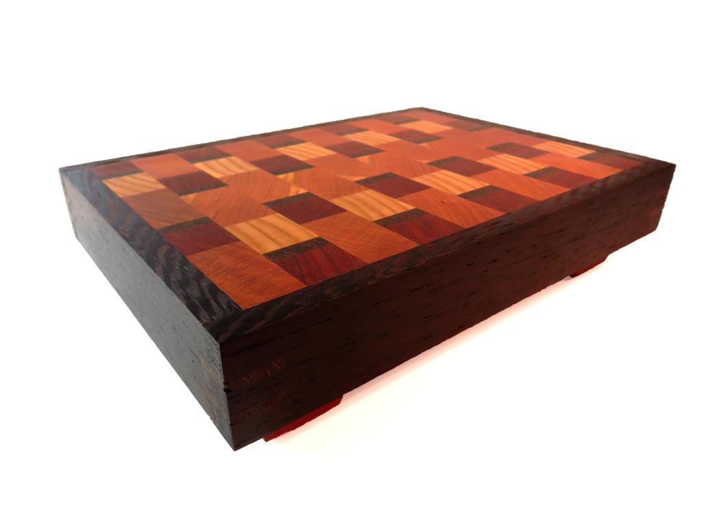 "Handmade wooden engrain cutting board big enough for your largest knife, but compact enough for a storage-challenged kitchen.  American cherry and ash, padauk with dramatic wenge border. Angled legs keep board above countertop moisture.  About 6 5/8"" x 9 1/8"" x 2 1/8"""