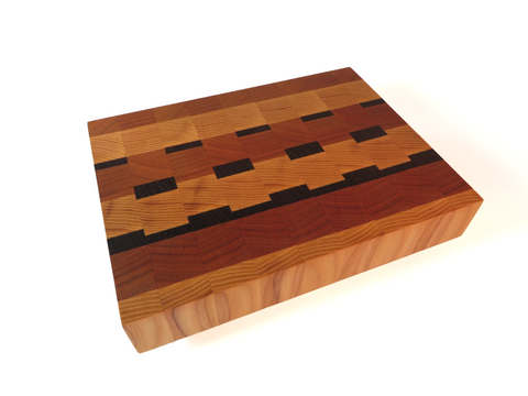 "Handmade wooden endgrain cutting board with enough room for veggies, but small enough to store in a studio kitchen.  American cherry, ash, and African wenge. Sturdy ash legs keep board above countertop moisture. About 6 1/2"" x 8 5/8"" x 2 3/8"""