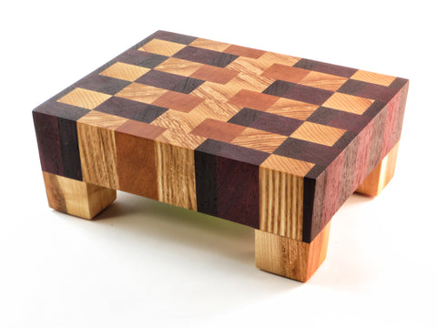 "Sweet little beauty of a handmade endgrain wooden cutting board. For dicing at the counter or serving at the table. American cherry and ash, African padauk and wenge. Elegant angled sides. Sturdy legs keep board above countertop moisture. About 7 1/8"" x 5 3/4"" x 2 3/4"""