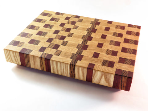 "Handmade endgrain wooden cutting board with trio of contrasting wood grains dancing across the surface. American ash accented with zebrawood and padauk. Angled legs keep board above countertop.  About 11 1/2"" x 8 3/4""x 2 1/8"""