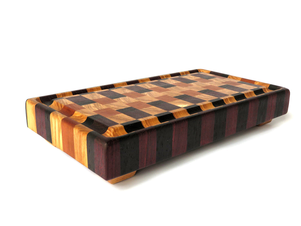 "Four woods blend into one contemporary grid, for a handmade endgrain wooden cutting board with all our best functional features. American ash and cherry, plus wenge and padauk. Gutter keeps juice off your table and angled legs keep board above countertop moisture. About 12 7/8"" x 7"" x 2 1/4"""