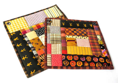 "Golden brown, with swirls of black and pink. Each handmade potholder includes unique pieces of vintage quilt blocks, combined with contemporary quilting cottons. Two squares per set (about 8 3/4"" and 10""). A one-of-a-kind house-warming gift."