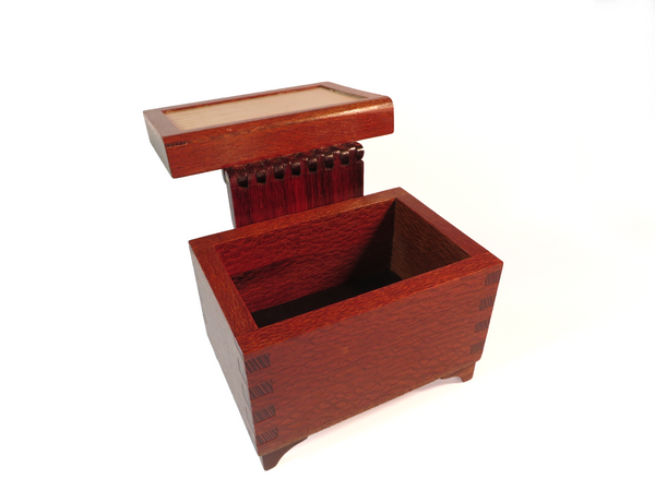 "Striking one-of-a-kind handmade wooden box for ""man stuff."" Solid lacewood body with unique padauk hinge. High-contrast inset of curly maple and tapered walnut legs. About 6 5/16"" x 4 1/4""x 5 1/8""H"