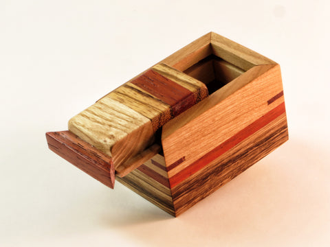 "Tiny, colorful handmade wooden box with secret slider top. Ash, zebrawood, padauk and cherry. About 2 7/8"" x 1 7/8"" x 2"" H"