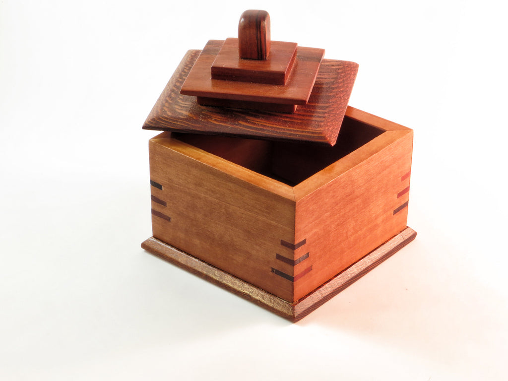 "Deep red hues of cherry and lacewood echo one another in diminutive but dramatic one-of-a-kind handmade wooden box. About 3 1/2"" sq x 4""H"