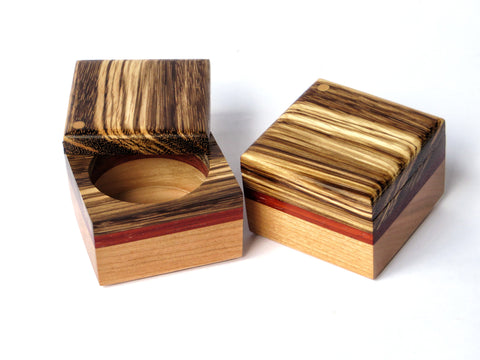 "Try this artistic yet functional handmade wooden box for salt, pepper or any spice you want in a pinch. Cherry and padauk, with zebrawood top on brass pin. About 2 1/4"" sq x 1 5/8"" H"