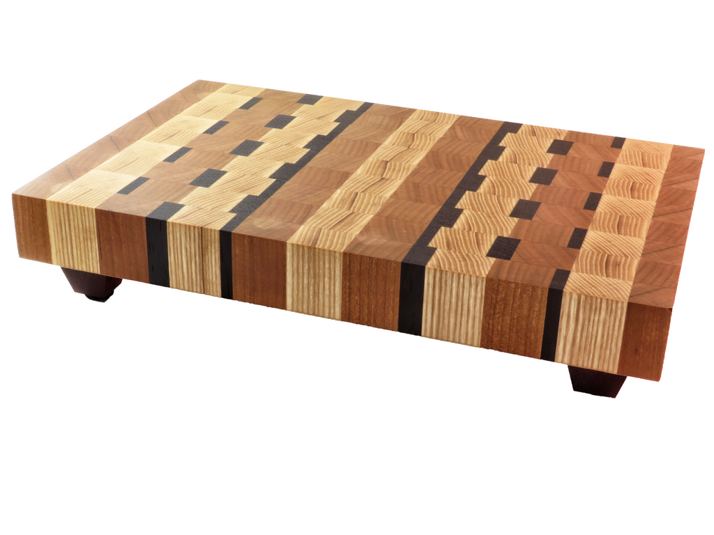"Handmade endgrain wooden cutting board with contemporary grid of American ash and cherry, with just a dash of wenge. Solid legs keep board well above countertop moisture (and they're cute, too). About 8 5/8"" x 13 1/8""x 2 1/2"""