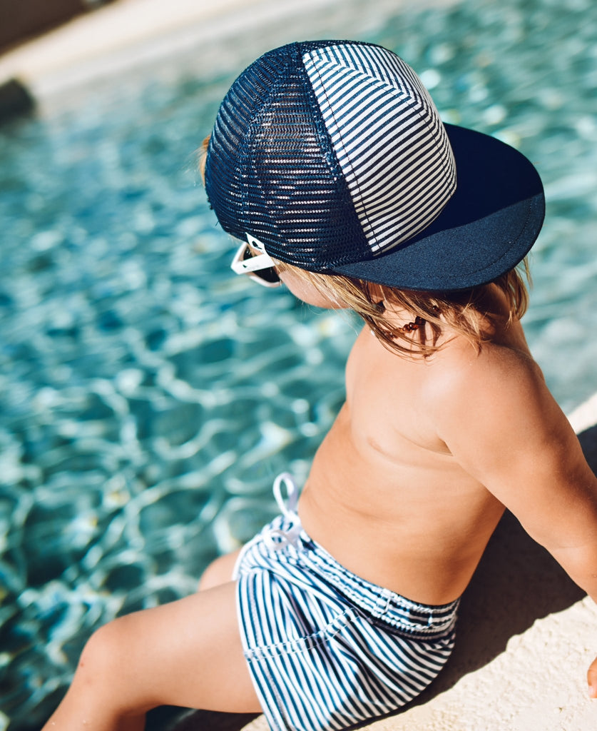 Image child by pool wearing Navy Stripe Swim Shorts from George Hats.