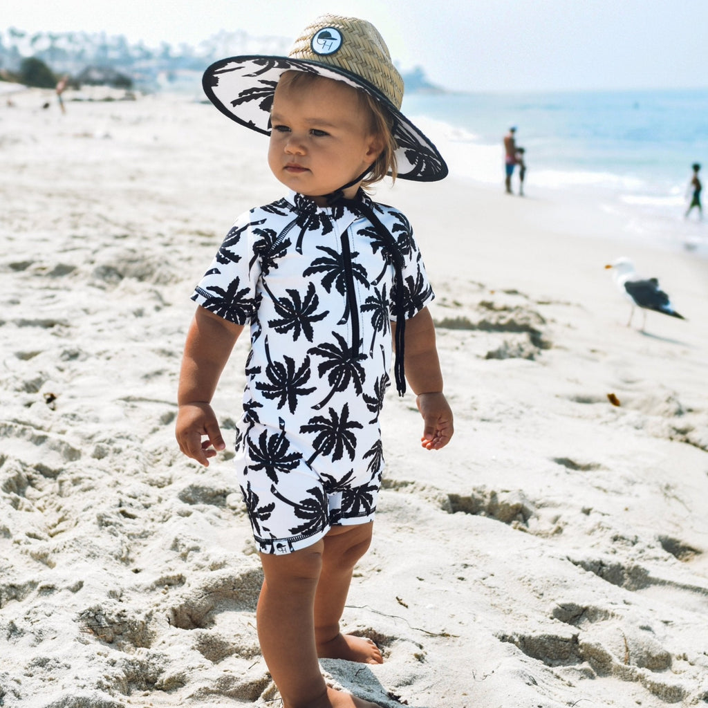 An image of a child in the George Hats Palm Straw Hat and Sunsuit.