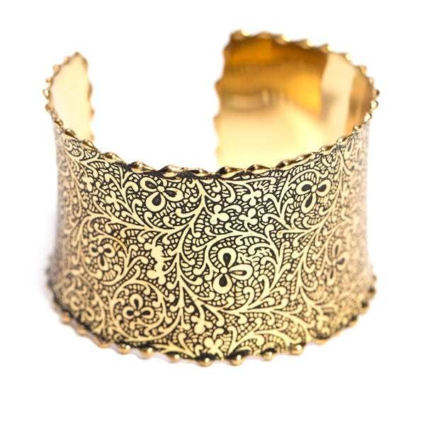 This gold-plated brass cuff is intricately hand-etched with vines and flowers making a beautiful bold statement. Adjustable and flattering on smaller wrists.