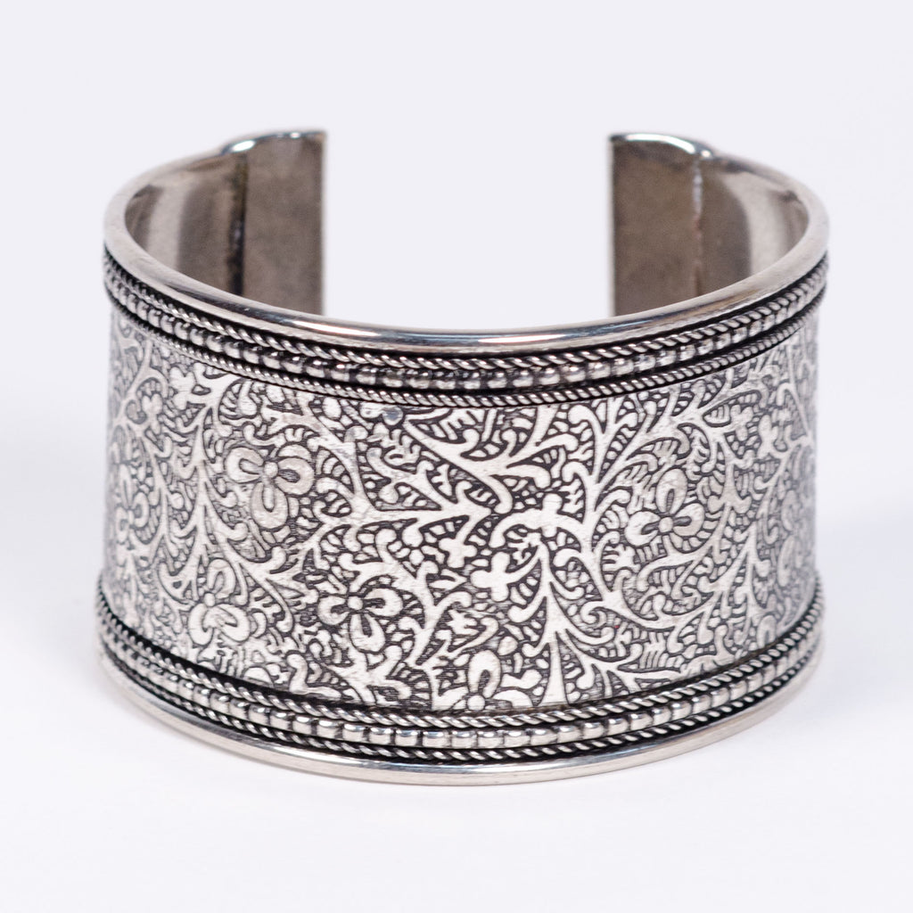 This silver-plated brass cuff is intricately hand-etched with vines and flowers making a beautiful bold statement. Adjustable and flattering on smaller wrists.