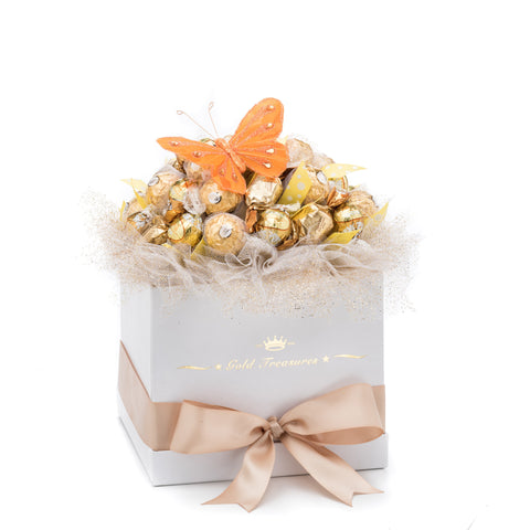 U can see chocolate edible bouquet in white box with gold ribbon. On the top of the box is gold tulle with yellow polka dots ribbons featuring Ferrero Rocher chocolates, Godiva milk caramels truffles and Lindt white truffles all together 35. The orange butterfly is sitting on the top of the bouquet.