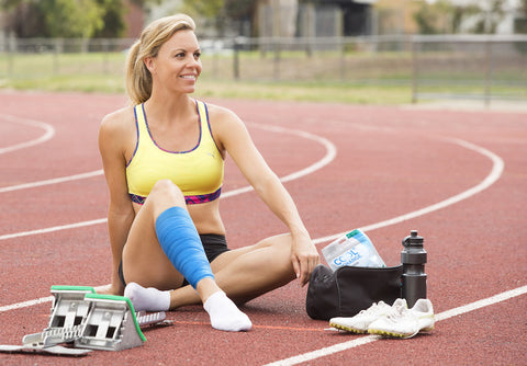 woman with CoolXChange compression wrap stretching on track