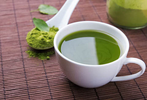 Green Matcha tea in a white cup with a spoon behind it