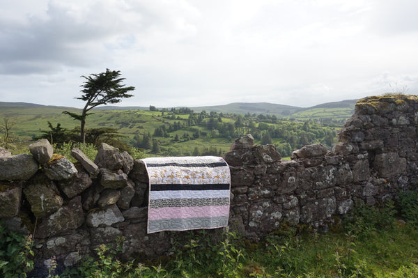 pink and black quilt hanging on a stone wall