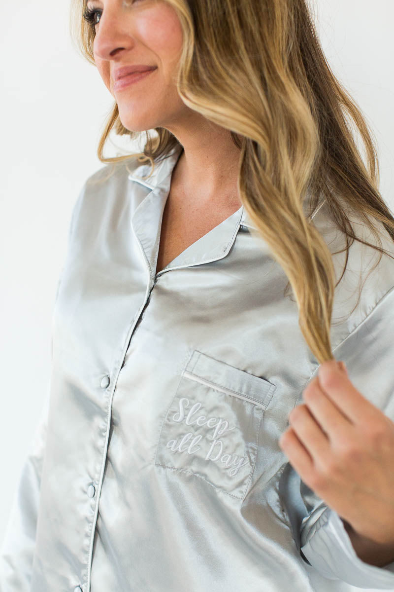 Close-Up View of Satin Pajama Set in Glacier Gray with Matching Long-Sleeved Top and Pant Bottom that Features an Embroidered Side Chest Pocket that Reads Sleep All Day in White Text