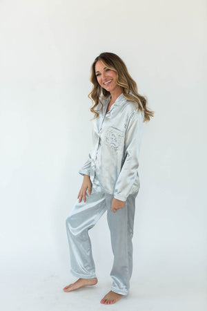 Satin Pajama Set in Glacier Gray with Matching Long-Sleeved Top and Pant Bottom that Features an Embroidered Side Chest Pocket that Reads Sleep All Day in White Text