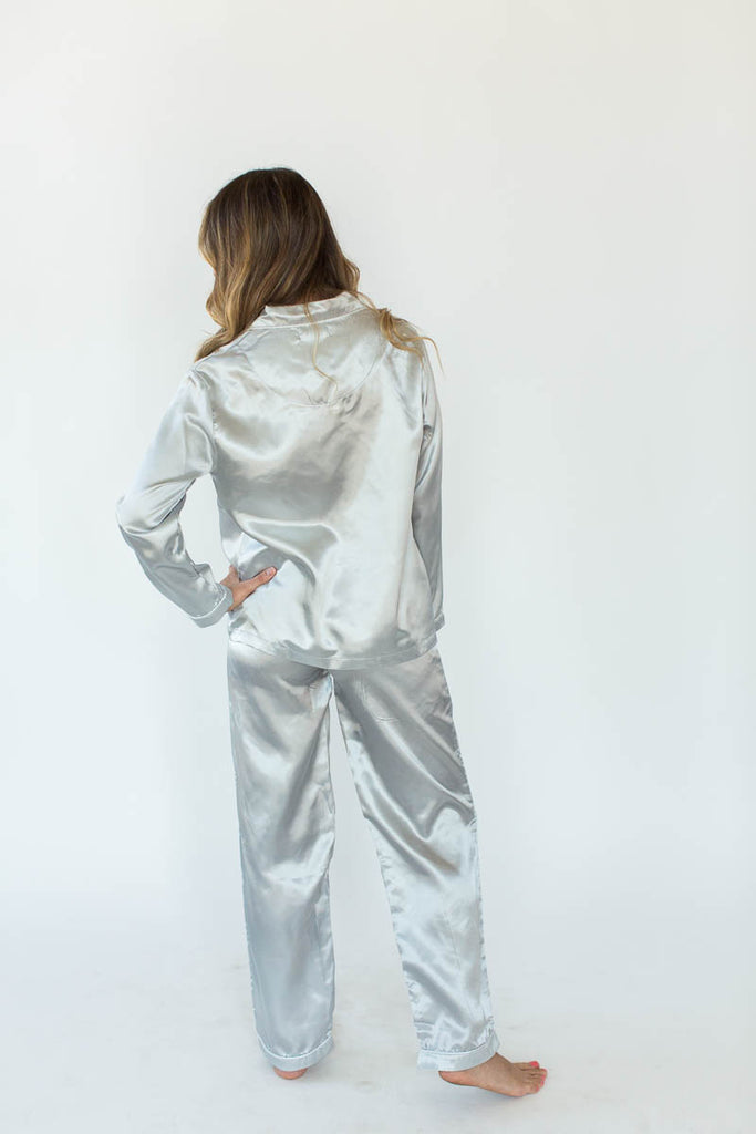 Back View of Satin Pajama Set in Glacier Gray with Matching Long-Sleeved Top and Pant Bottom that Features an Embroidered Side Chest Pocket that Reads Sleep All Day in White Text