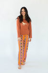 Southwestern Pajama Set that Features a Burnt Orange Top with A Horse Mustang Print in the Center & Correlating Pants with an Orange, Yellow, & Purple Southwestern Print Design